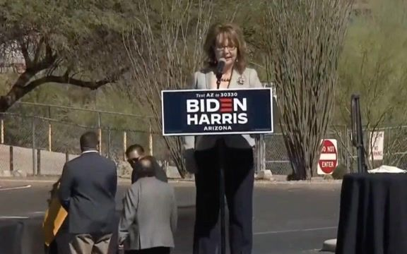 Former U.S. Congresswoman Gabby Giffords does a little dance to the honking of horns at a Biden event.